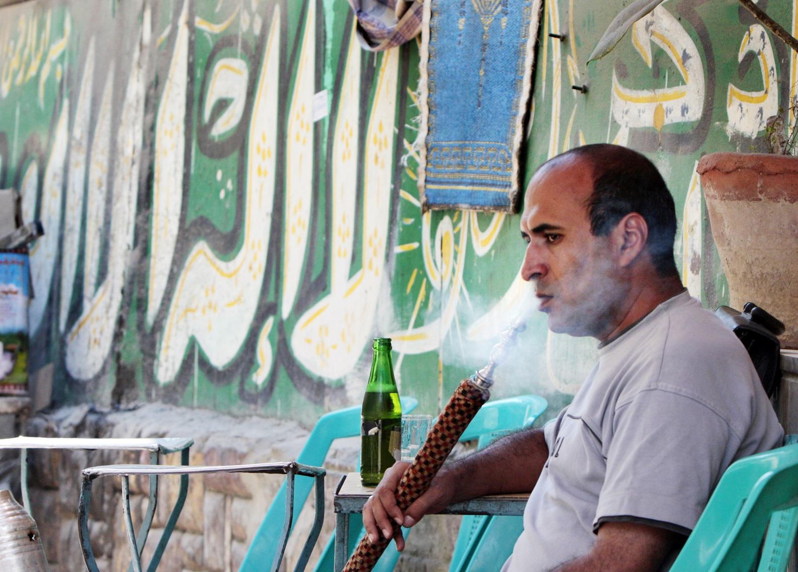 A man smoking shisha the traditional way